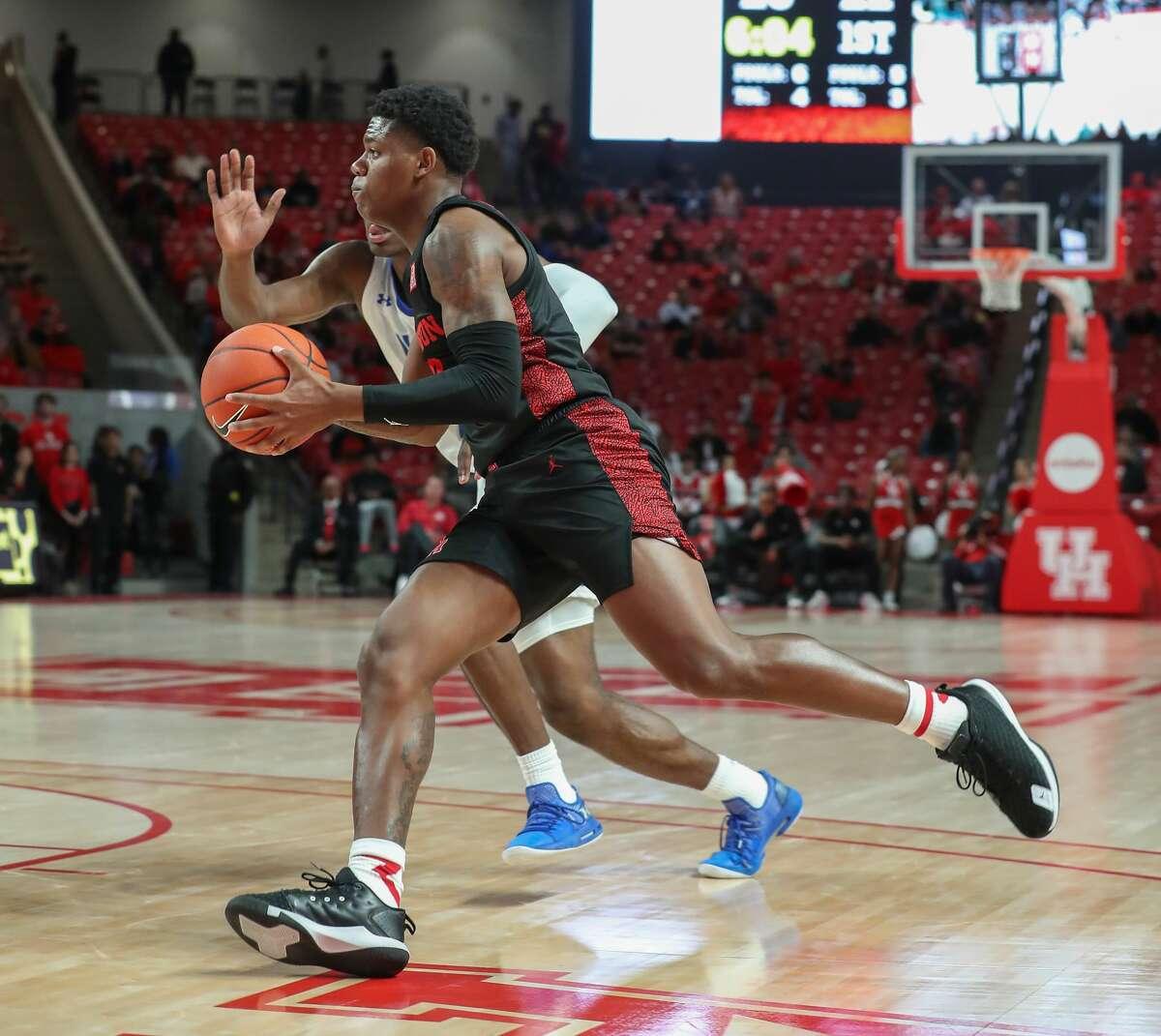 Houston Cougars guard Marcus Sasser (0)drives around Texas-Arlington Mavericks forward Jordan Phillips (2) during the first half of an NCAA basketball game at Fertitta Center Wednesday, Dec. 11, 2019, in Houston.