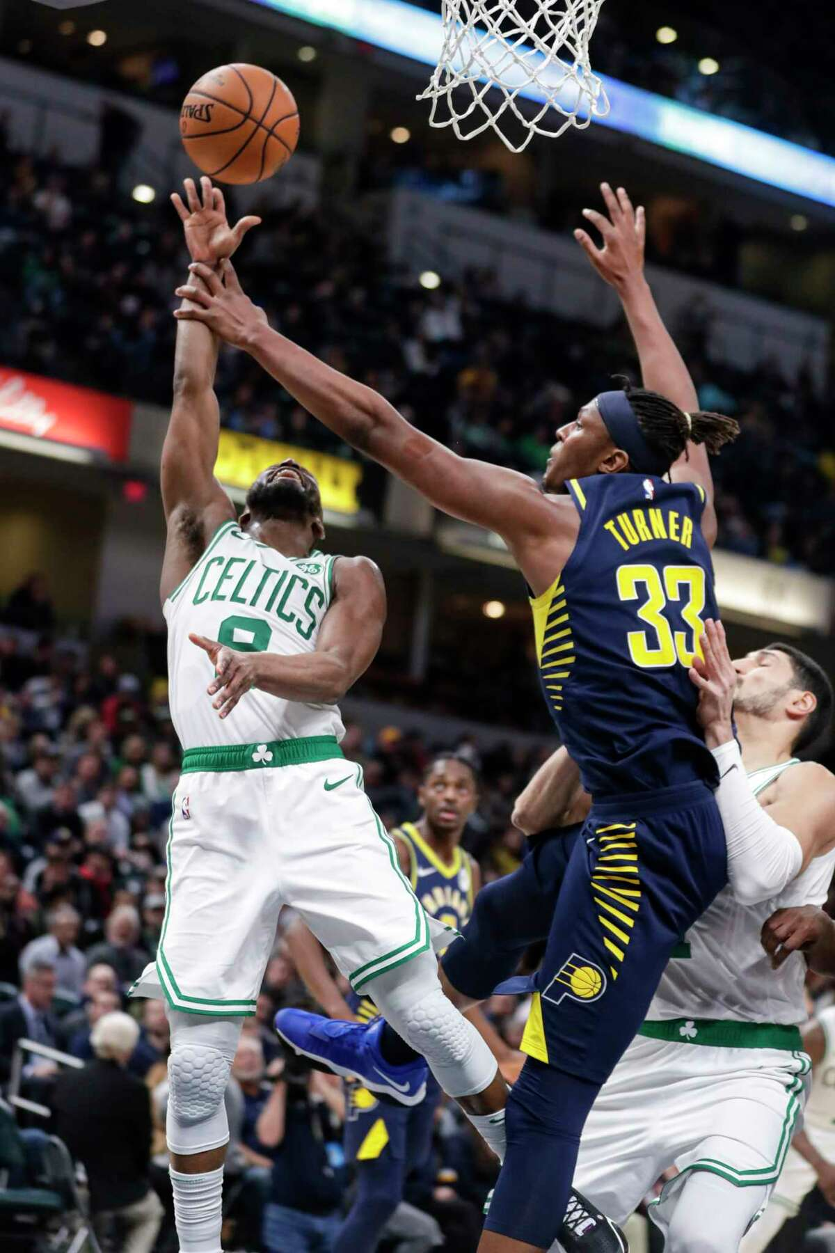 Indiana Pacers center Myles Turner (33) fouls Boston Celtics guard Kemba Walker (8) as he shoots during the second half of an NBA basketball game in Indianapolis, Wednesday, Dec. 11, 2019. The Pacers defeated the Celtics 122-117. (AP Photo/Michael Conroy)