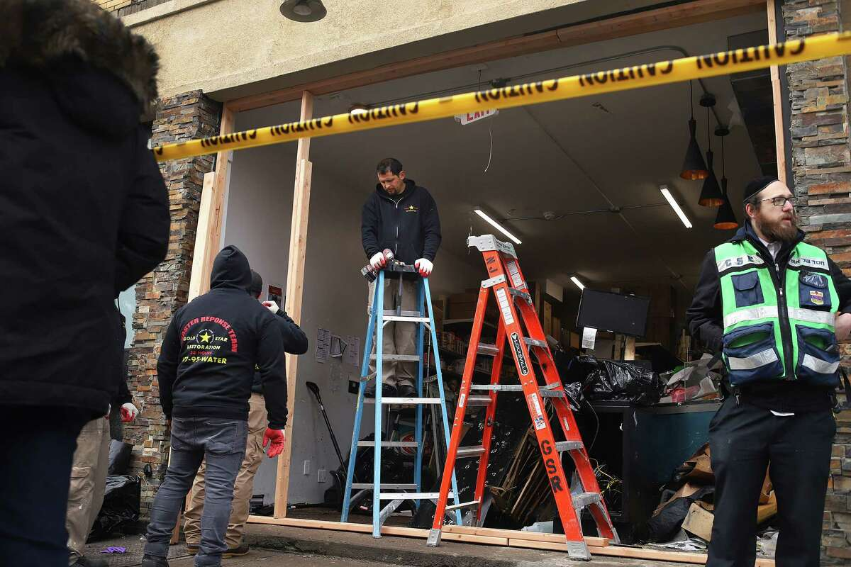 JERSEY CITY, NJ - DECEMBER 11: Recovery and clean up crews work to board up the JC Kosher Supermarket on December 11, 2019 in Jersey City, New Jersey. Six people, including a Jersey City police officer and three civilians were killed in a deadly, hours-long gun battle between two armed suspects and police on Tuesday in a standoff and shootout in a Jewish market that appears to have been targeted, according to Jersey City Mayor Steven Fulop. (Photo by Rick Loomis/Getty Images)