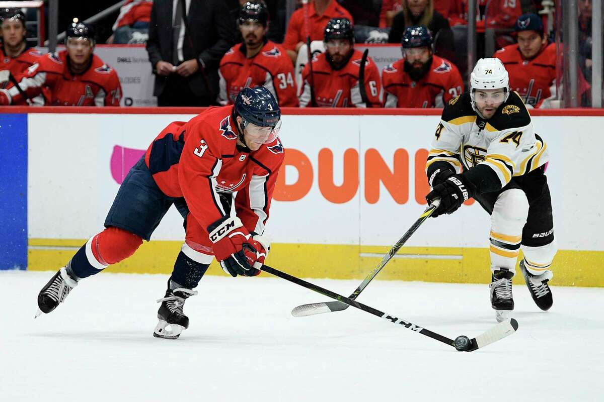 Washington Capitals defenseman Nick Jensen (3) and Boston Bruins left wing Jake DeBrusk (74) battle for the puck during the first period of an NHL hockey game, Wednesday, Dec. 11, 2019, in Washington. (AP Photo/Nick Wass)