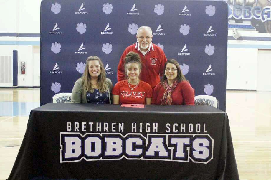 Megan Cordes (center) signs a letter of intent to play soccer at Olivet College next season and is joined by (from left) Brethren soccer coach Krystal Magee, father Marlen Cordes and mother Jennifer Cordes during a signing ceremony at the school on Wednesday. Photo: Kyle Kotecki/News Advocate