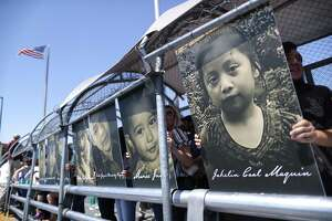 Activists hold photos of migrant children who died trying to cross the U.S.-Mexico border as they demonstrate standing on the Paso Del Norte Port of Entry bridge on June 27  in Ciudad Juárez, Mexico.