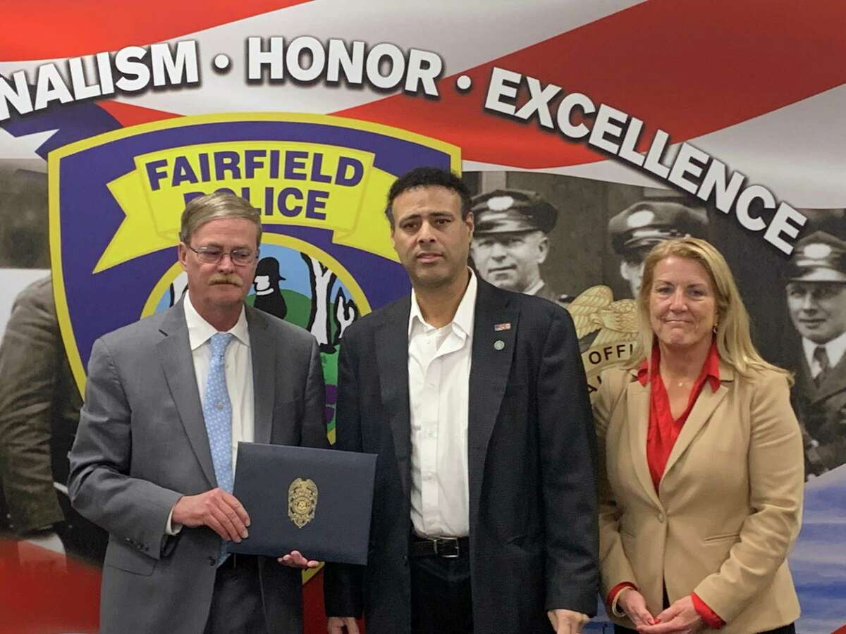 Police Lieutenant James Perez, center was honored by the town of Fairfield for saving a heart attack patient's life. He's shown here with Police Chief Christopher Lyddy and First Selectwoman Brenda Kupchick.