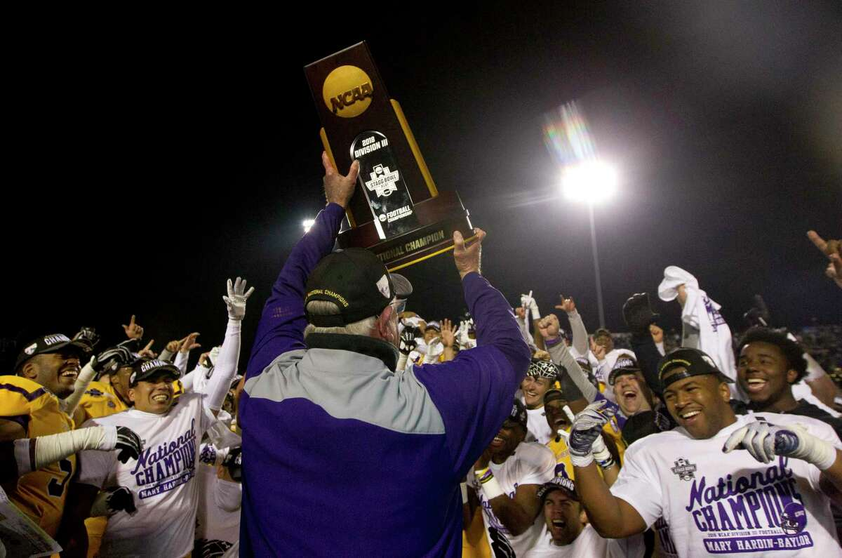 Mary Hardin-Baylor head coach Pete Fredenburg holds up the NCAA Division III college football championship trophy after defeating Mount Union 24-16 to win the Stagg Bowl at Woodforest Bank Stadium, Friday, Dec. 14, 2018, in Shenandoah.
