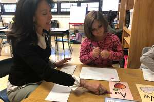 Deanna Toohey works with students in a classroom setting at Elizabeth Shelton School. Toohey, the school's reading specialist, was recently named the district's Innovative Educator for November.