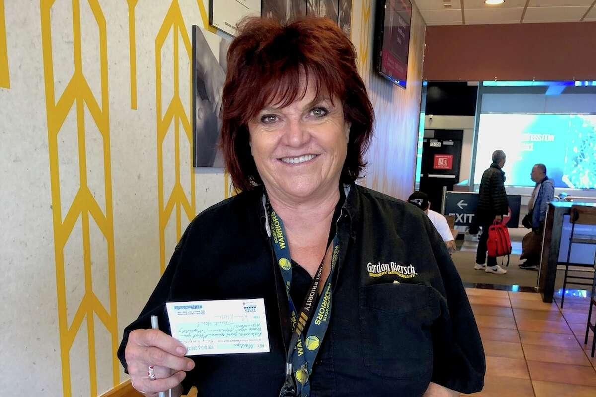Current photo of Marylin Pier at Gordon Biersch holding an #HMSHostShoutOut card, which recognizes great performance.