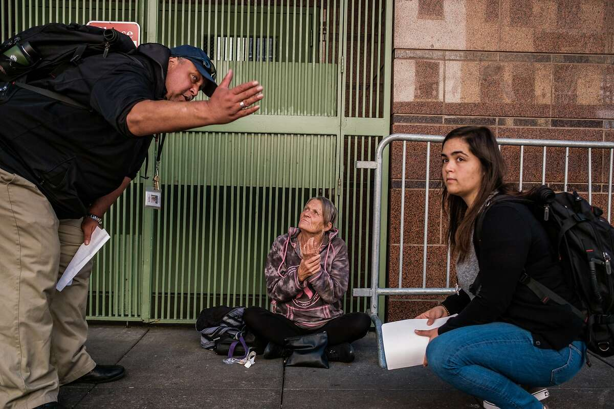 Eric Smith and Angel Bishoff of Health Right 360 speak with Diana Gomez, who is homeless, in San Francisco, Calif. on Thursday, October 17, 2019.