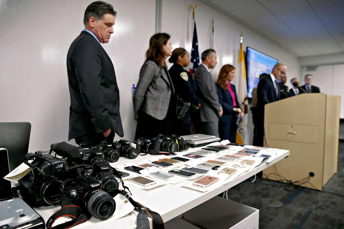 Sean Connolly (left), a prosecutor with the District Attorney's office, stands near recovered electronic equipment displayed during a news conference in San Francisco, Calif. on Thursday, Dec. 12, 2019 to announce the seizure of more than $2 million of stolen property following a multi-agency investigation called Operation Focus Lens. Connolly leads the group in the DA�s office that led the operation.
