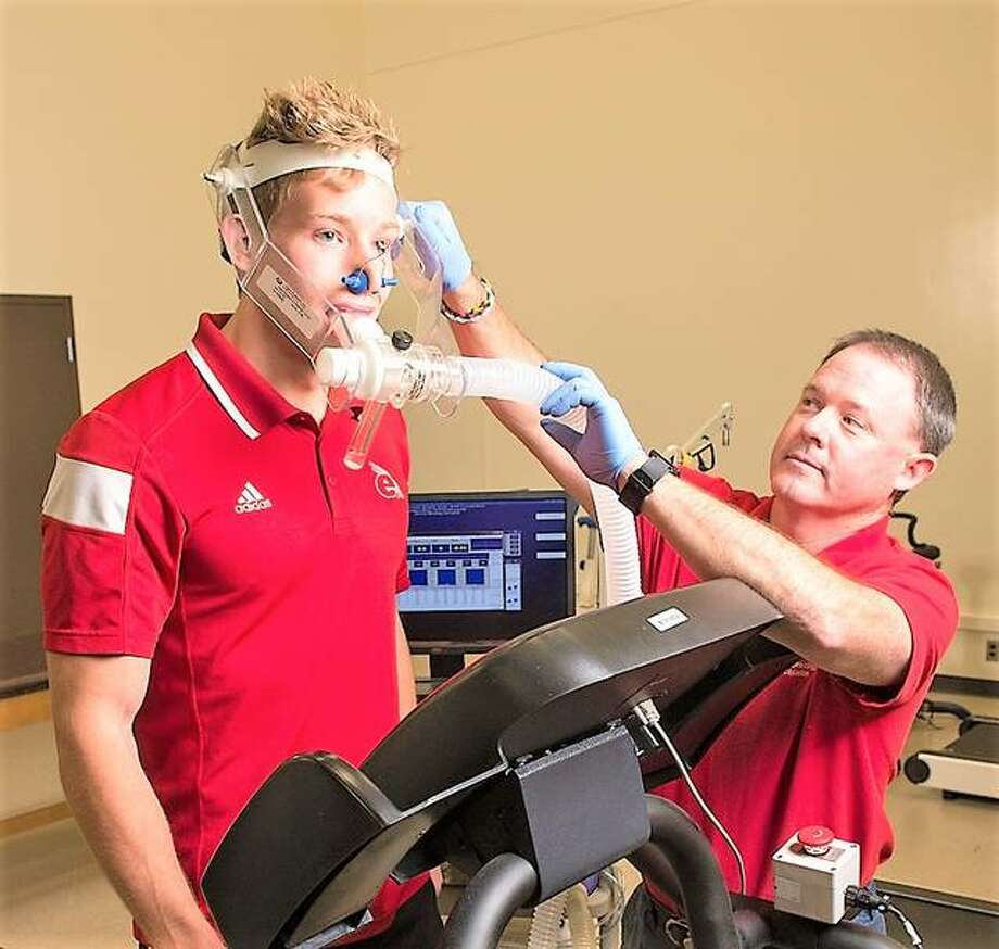 SIUE's Bryan Smith, associate professor, works with a student in an exercise science lab.