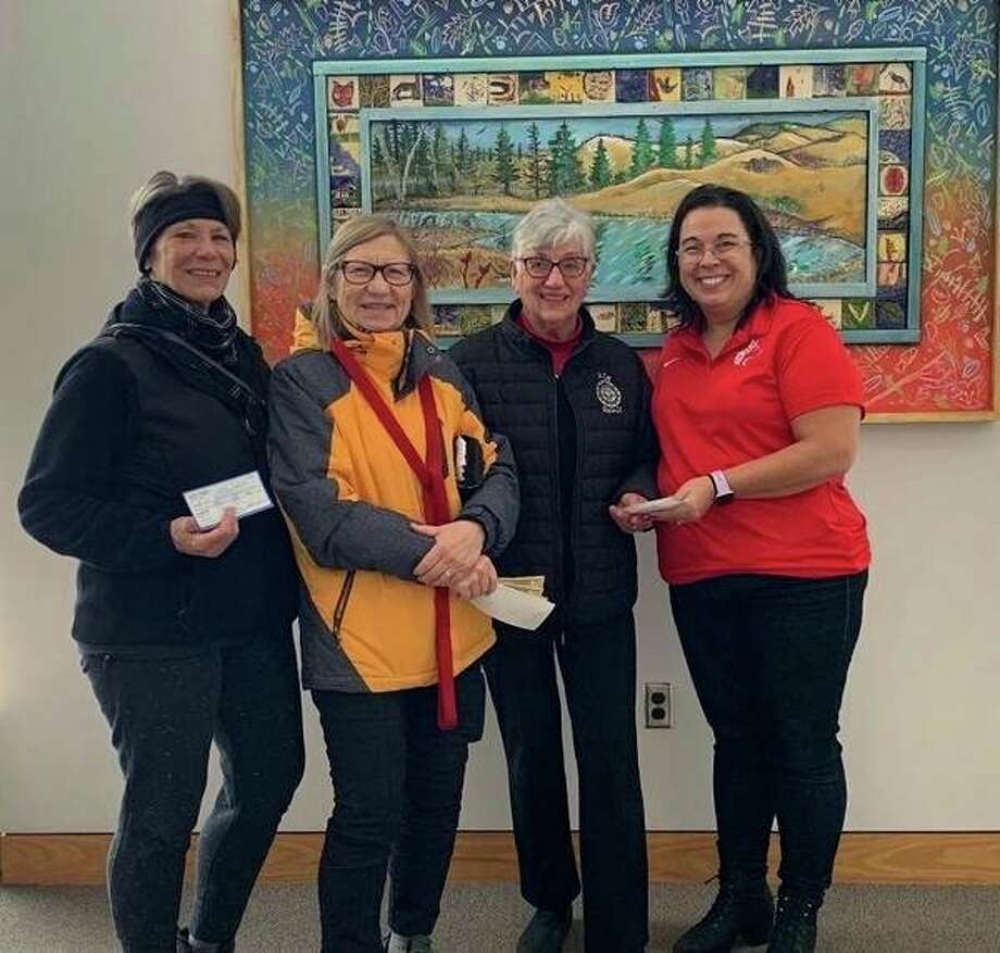 Barbara Schneider,Bonnie Nescot and Sharon Rose (pictured left to right) present a check to Lisa Purchase (far right) to help pay off student lunch debt at Benzie Central Schools. (Submitted photo)