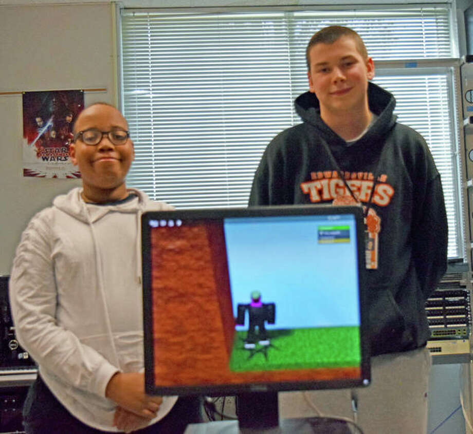"Sam Msengi, left, and Connor Sweet stand behind a computer at Edwardsville High School that has their game, ""Quest for the Golden Head,"" displayed. The game won the 2019 Congressional App Challenge for the 13th District of Illinois. Photo: Tyler Pletsch 