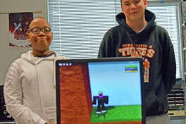 "Sam Msengi, left, and Connor Sweet stand behind a computer at Edwardsville High School that has their game, ""Quest for the Golden Head,"" displayed. The game won the 2019 Congressional App Challenge for the 13th District of Illinois."