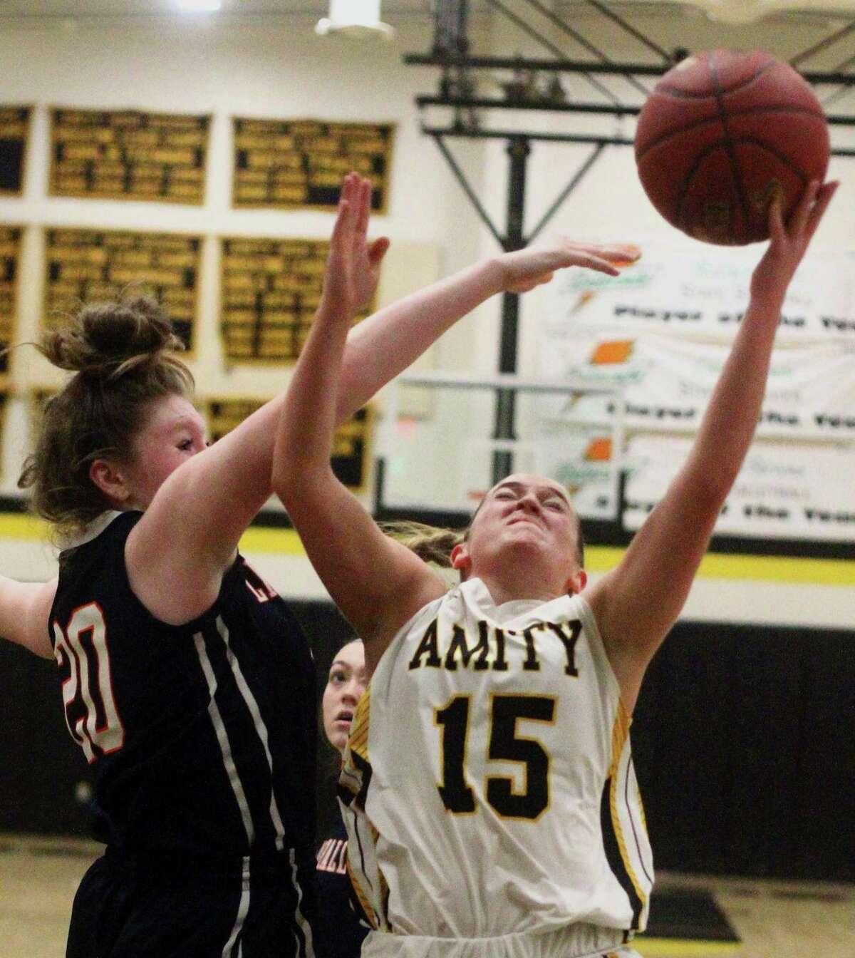 Amity's Jillian Martin (15) looks to score as Lyman Hall's Theresa Lynch (20) blocks during basketball action in Woodbridge, Conn., on Thursday Dec. 13, 2018.