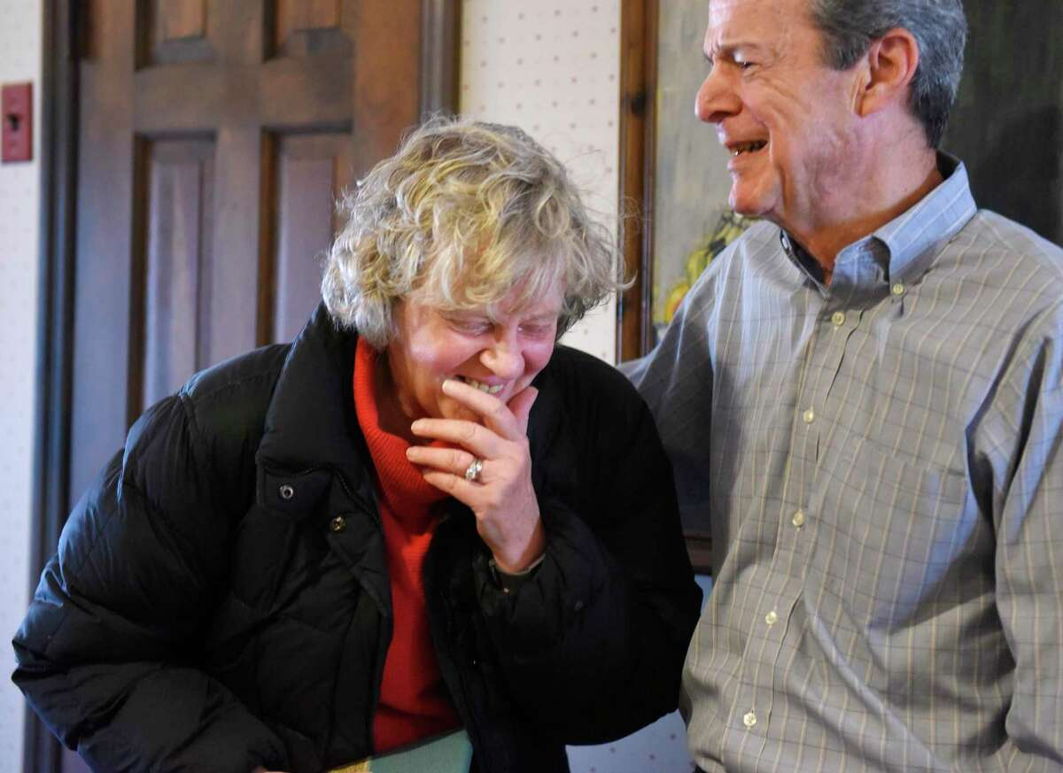 Cathy Ostuw, co-founder of Building One Community, smiles beside her husband, Rich Ostuw, after being surprised at a friend's home in Stamford, Conn. to learn that she is this year's Stamford Citizen of the Year winner on Thursday, Dec. 12, 2019. Ostuw was heading to her weekly Scrabble game with friends when Mayor David Martin and dozens of friends and colleagues suprised her with the honor, which is sponsored by Post 142 of the Jewish War Veterans of the United States. Building One Community's mission is to advance the successful integration of immigrants and their families.