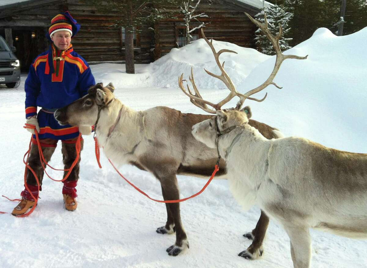In this March 2013 photo, A Sami handler in traditional clothing holds two of his herd in Saariselka, Finnish Lapland. Reindeer are featured on Christmas cards and in movies worldwide this time of year, galloping across the sky with Santaâ s sleigh in tow. But on Europeâ s northern fringe, the migratory mammals are part of everyday life all year round as they roam the fells of Lapland - the Arctic homeland of the indigenous Sami people of Norway, Sweden, Finland and northwest Russia. (AP Photo/ David McDougall)