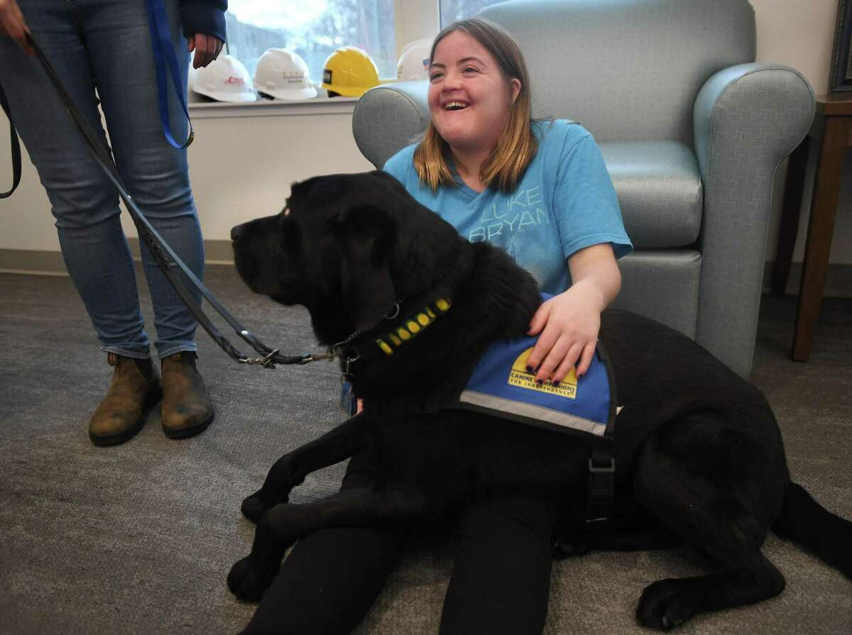 Chapel Haven Schleifer Center resident Bryn Hildebrand visits with therapy dog Preston during his daily rounds at the center in New Haven Dec. 5, 2019.