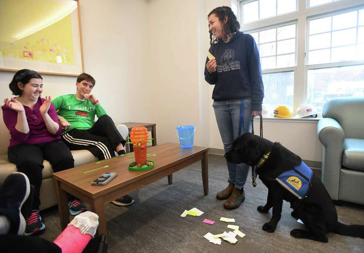 From left, residents Sarah Thomas and Nick Wiant enjoy time with therapy dog Preston and his handler, special education teacher Danielle Drazen, at the Chapel Haven Schleifer Center in New Haven Dec. 5. One of the dog's special skills is that he is able to randomly draw a slip of paper for a weekly prize drawing for residents.