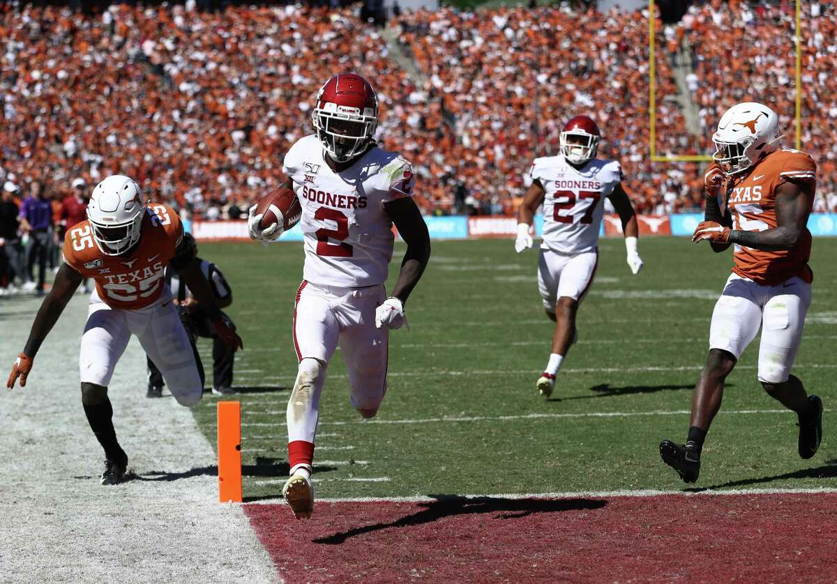 DALLAS, TEXAS - OCTOBER 12: CeeDee Lamb #2 of the Oklahoma Sooners runs for a touchdown against B.J. Foster #25 of the Texas Longhorns in the third quarter during the 2019 AT&T Red River Showdown at Cotton Bowl on October 12, 2019 in Dallas, Texas.
