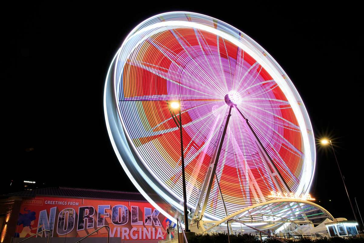 Bright lights on the SkyStar ferris wheel flash in a variety of patterns at Waterside in Norfolk on Tuesday, July 31, 2018. The traveling ferris wheel opened for business in Norfolk in May, and was removed at the end of August.