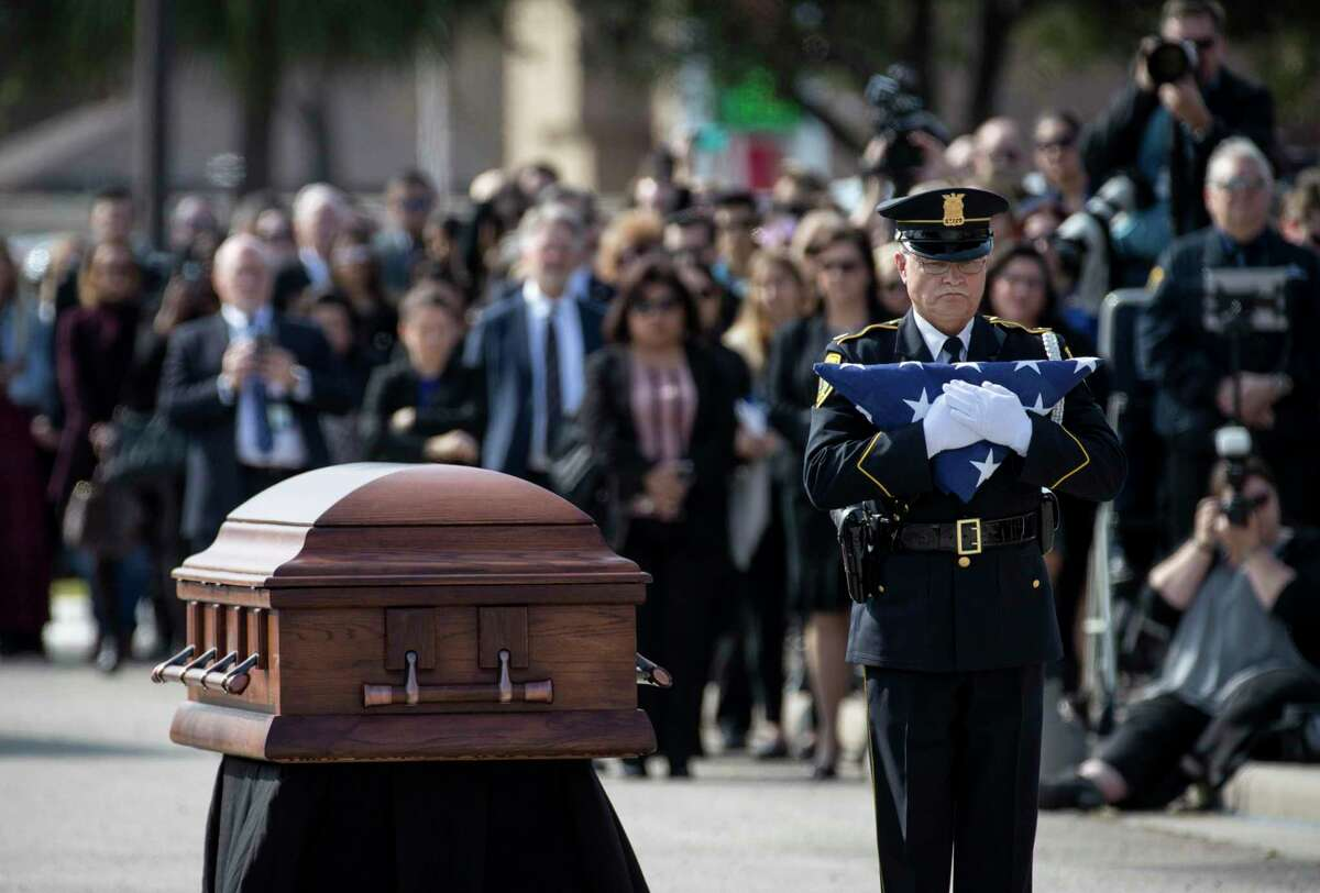 An officer from the Houston Police Honor Guard carries a folded American flag during the funeral for Houston police Sgt. Christopher Brewster on Thursday, Dec. 12, 2019, in Houston. Brewster was shot and killed in the line of duty while responding to a domestic violence call.