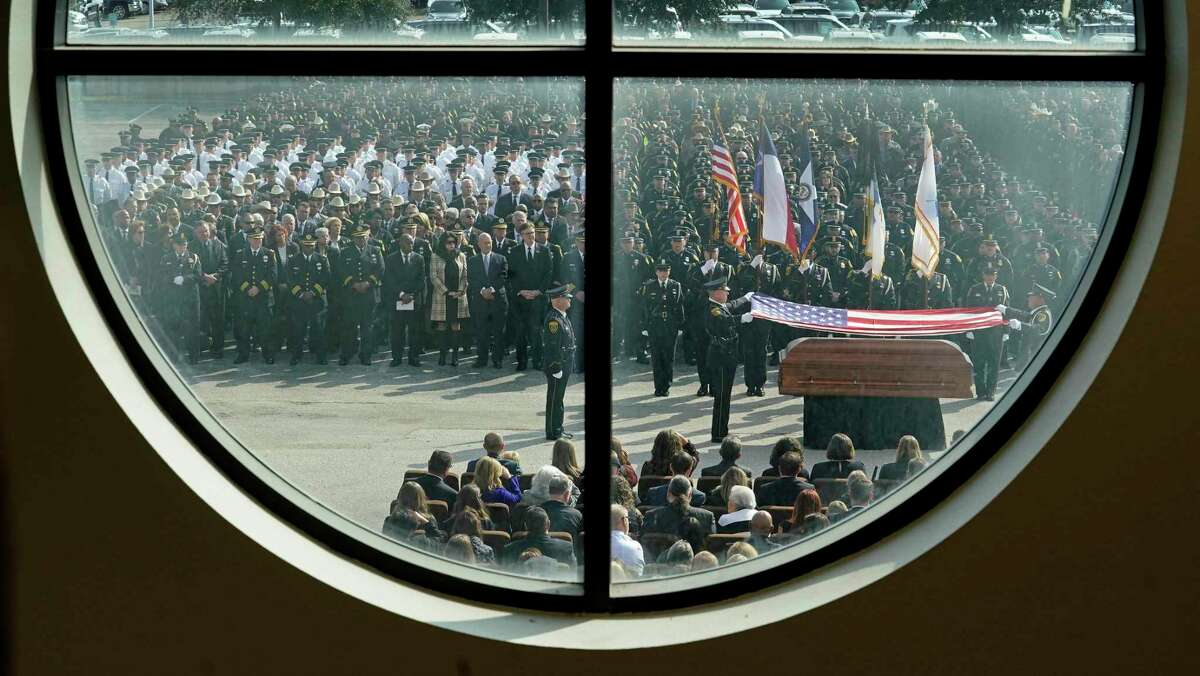 Shown through a church window, Houston Police Honor Guard members fold the flag from the casket of HPD Sgt. Christopher Brewster during an honor ceremony after his funeral service at the church, Thursday, Dec. 12, 2019. Brewster, 32, was gunned down Saturday evening while responding to a domestic violence call. Police arrested 25-year-old Arturo Solis that night in the shooting death. Solis faces capital murder charges.