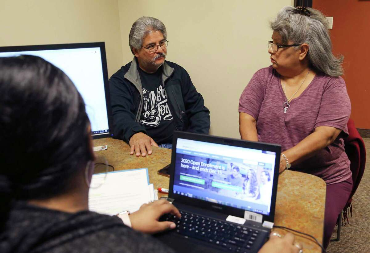 David Ponce, 59, and his wife, Mary, 56, look over options for medical insurance through the federal exchange at the EnrollSA offices. They found it too expensive.