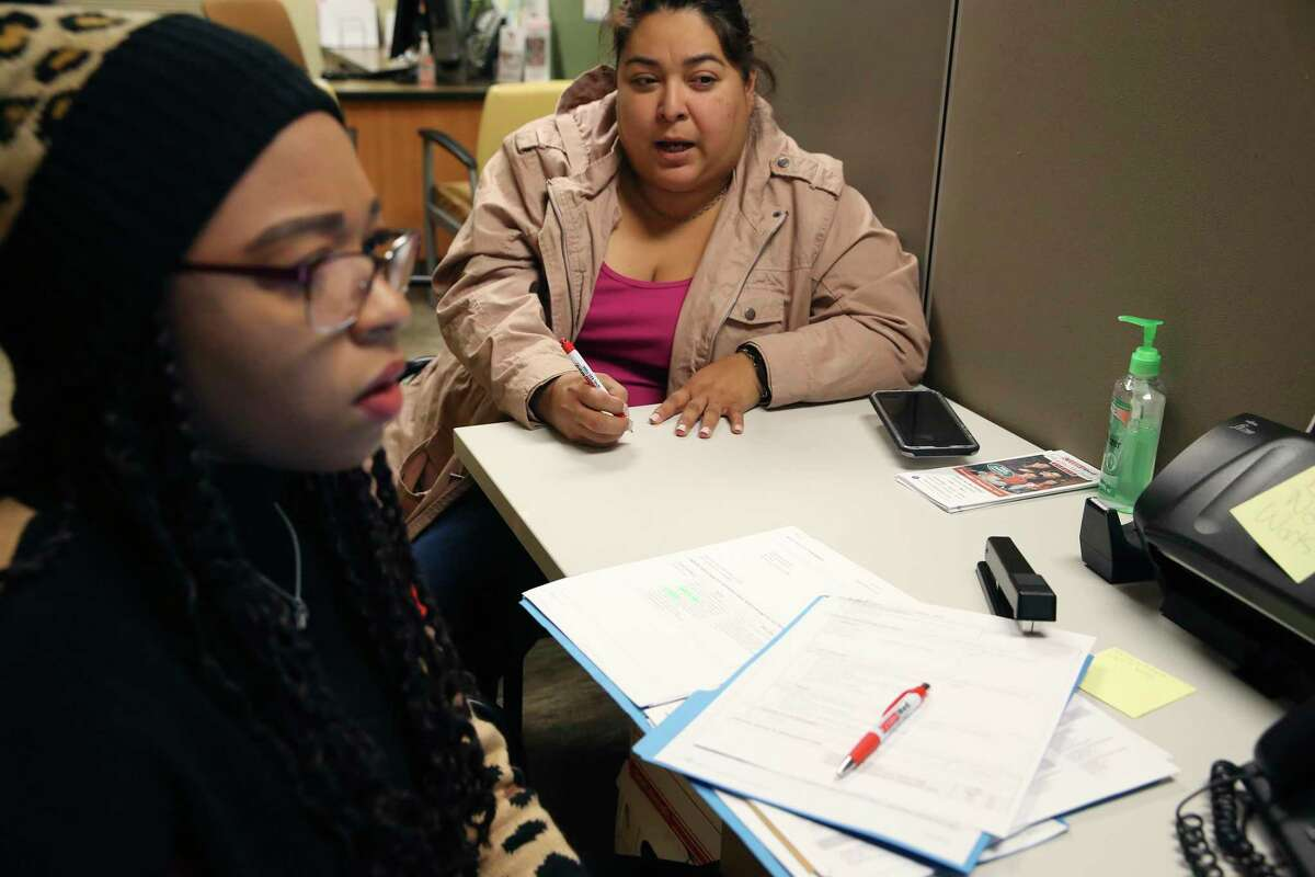 Stephanie Gutierrez, 43, right, reenrolls for medical insurances that includes her daughter, with the help from Certified Application Counselor Kytheranialynn Montez at the EnrollSA offices inside the CentroMed south side clinic, Thursday, Dec. 12, 2019. It was the third year Gutierrez has enrolled for insurance on the federal exchange. The deadline for enrollment is Dec. 15. Nearly 18-percent of adults in Texas have no coverage.