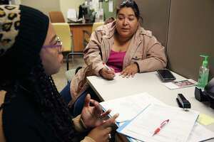 Stephanie Gutierrez, 43, right, renews her medical insurance with the help of certified application counselor Kytheranialynn Montez on Thursday at the EnrollSA offices at the South Side CentroMed clinic.