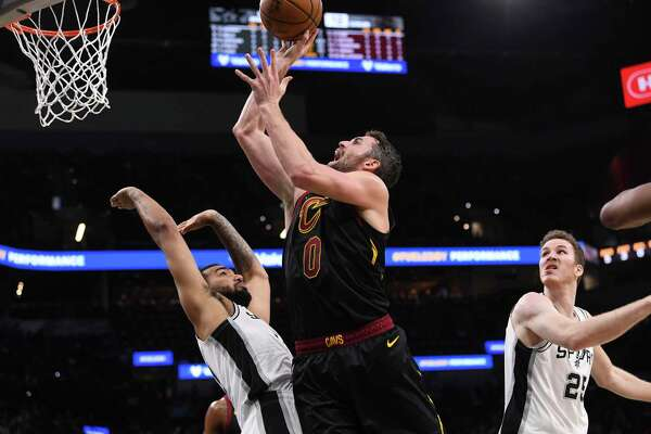 Kevin Love of the Cleveland Cavaliers (0) shoots as San Antonio Spurs Trey Lyles, left, and Jakob Poeltl, right, defend during first-half NBA action in the AT&T Center on Thursday, Dec. 12, 2019.