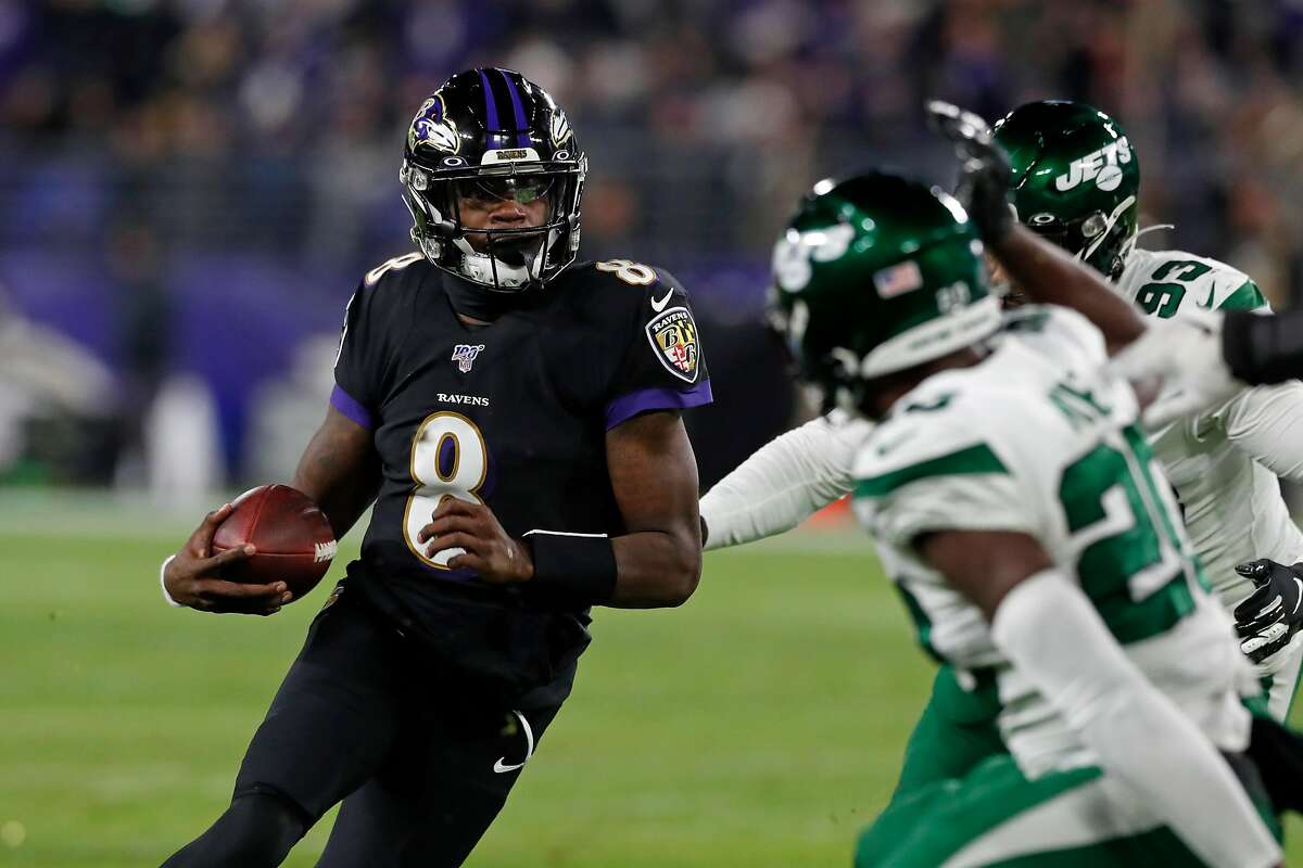 BALTIMORE, MARYLAND - DECEMBER 12: Quarterback Lamar Jackson #8 of the Baltimore Ravens breaks NFL single season record for rushing yards by a quarterback, formerly held by Michael Vick in the first quarter of the game at M&T Bank Stadium on December 12, 2019 in Baltimore, Maryland. (Photo by Todd Olszewski/Getty Images)