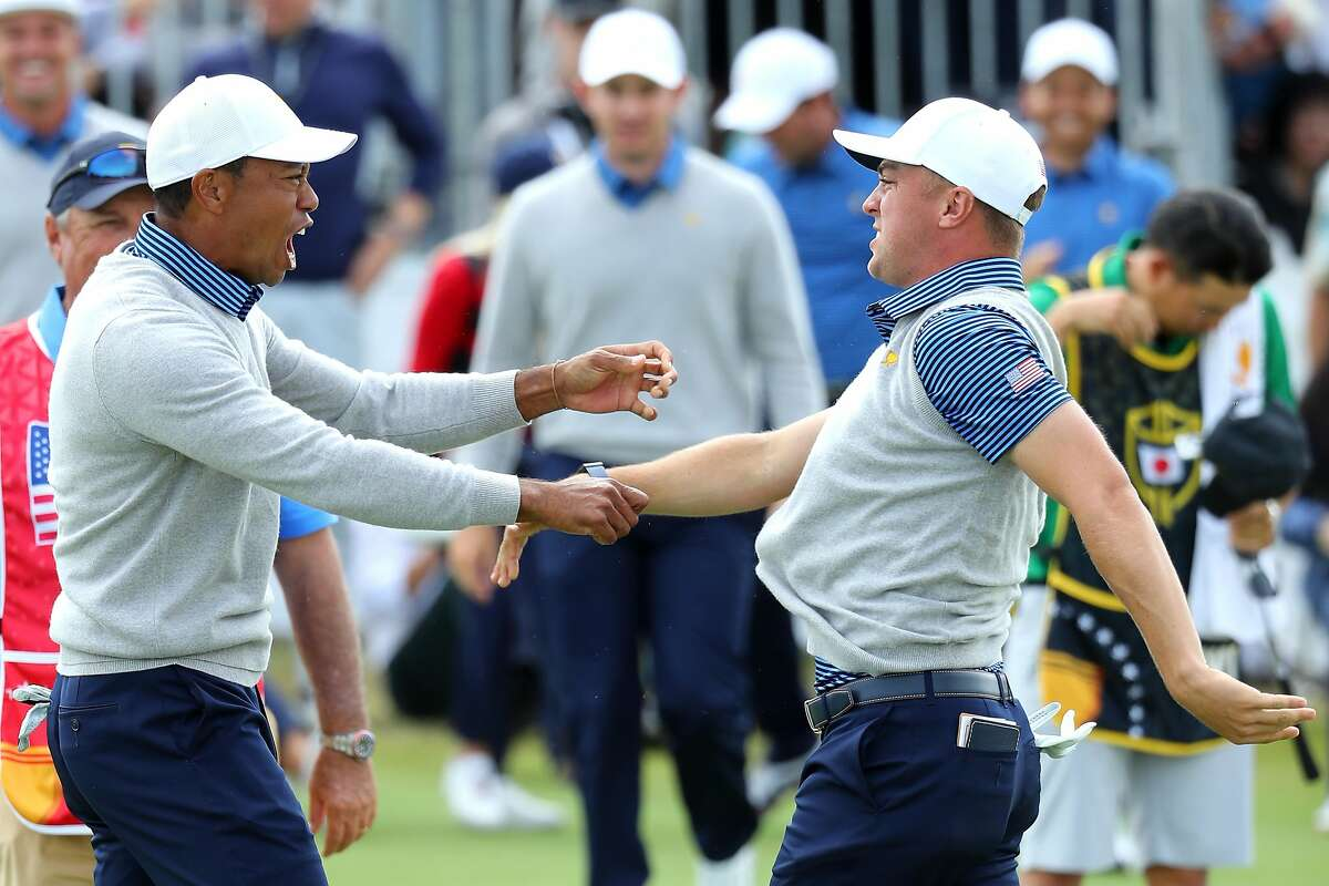 MELBOURNE, AUSTRALIA - DECEMBER 13: Playing Captain Tiger Woods of the United States team and Justin Thomas of the United States team celebrate defeating Byeong-Hun An of South Korea and the International team and Hideki Matsuyama of Japan and the International team 1up on the 18th green during Friday foursome matches on day two of the 2019 Presidents Cup at Royal Melbourne Golf Course on December 13, 2019 in Melbourne, Australia. (Photo by Warren Little/Getty Images)