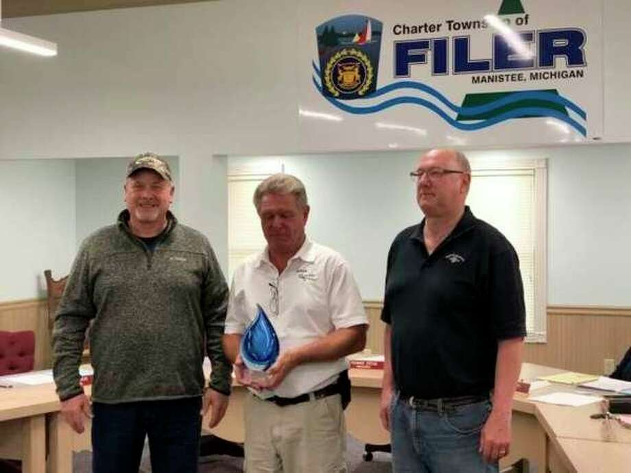 Mike Hiller (left), FilerTownship water operator, and Tom Stege (right), Filer Township treasurer, receive the award from Brian Minor, of the Michigan Rural Water Association. Hiller will represent Michigan at the National Water Taste Off Competition Feb. 3-6. (Courtesy Photo/Terry Walker)