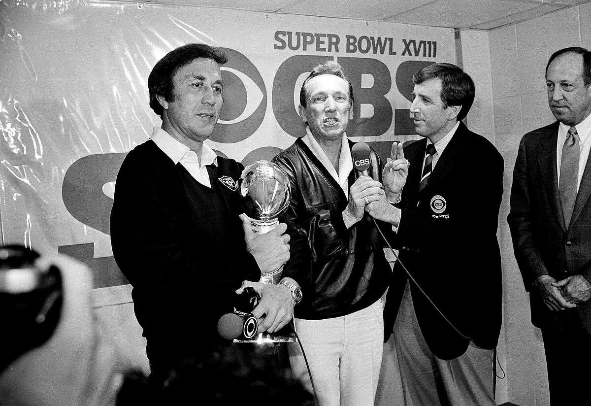 Raiders coach Tom Flores clutches the Super Bowl trophy as Raiders managing general partner Al Davis is interviewed by Brent Musburger in the locker room after their 38-9 win over the Washington Redskins in Super Bowl XVIII at Tampa Stadium Jan. 23, 1984. At right is NFL Commissioner Pete Rozelle.