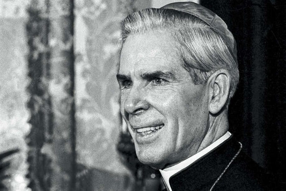 Bishop Fulton J. Sheen is seen in October 1966 in his office at the Propagation of Faith in New York. Sheen, who before his death in 1979 was famous for his radio and TV preaching, had been scheduled to be beatified — the last step before sainthood — in a Dec. 21 ceremony in Peoria. However, the Vatican recently took the rare step of indefinitely postponing the ceremony at the request of the Rochester, New York, diocese, which said more time was needed for further investigations. Photo: Eddie Adams | Associated Press
