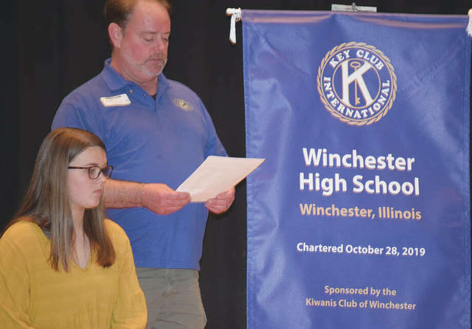 Key Club President Millie Lashmett (left) listens Tuesday as Winchester Kiwanis Club President Chuck Frost speaks during the Key Club's induction ceremony at Winchester High School.