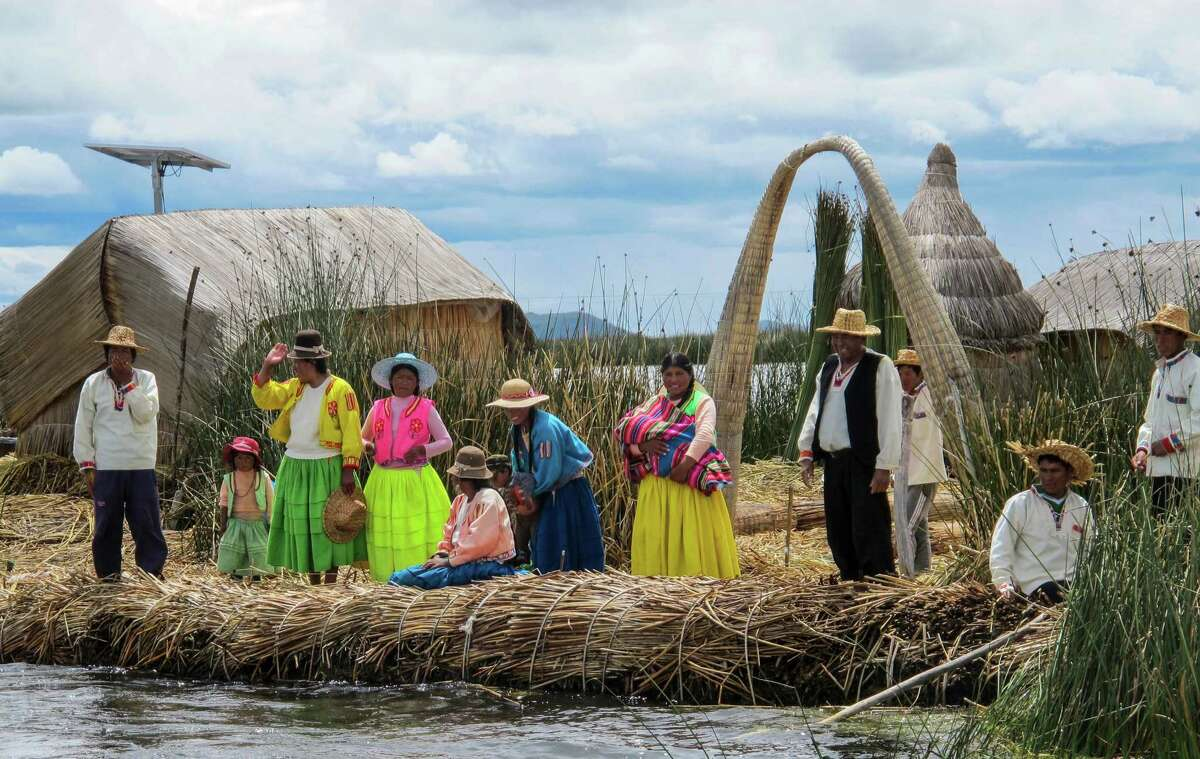 LAKE TITICACA, PERU - Grateful for visitors, Antonio Jullahui and the other residents of a floating island on Lake Titicaca gather to wave goodbye to their departing guests. The Uros economy is largely depended upon tourism. (Thomas Curwen/TNS)