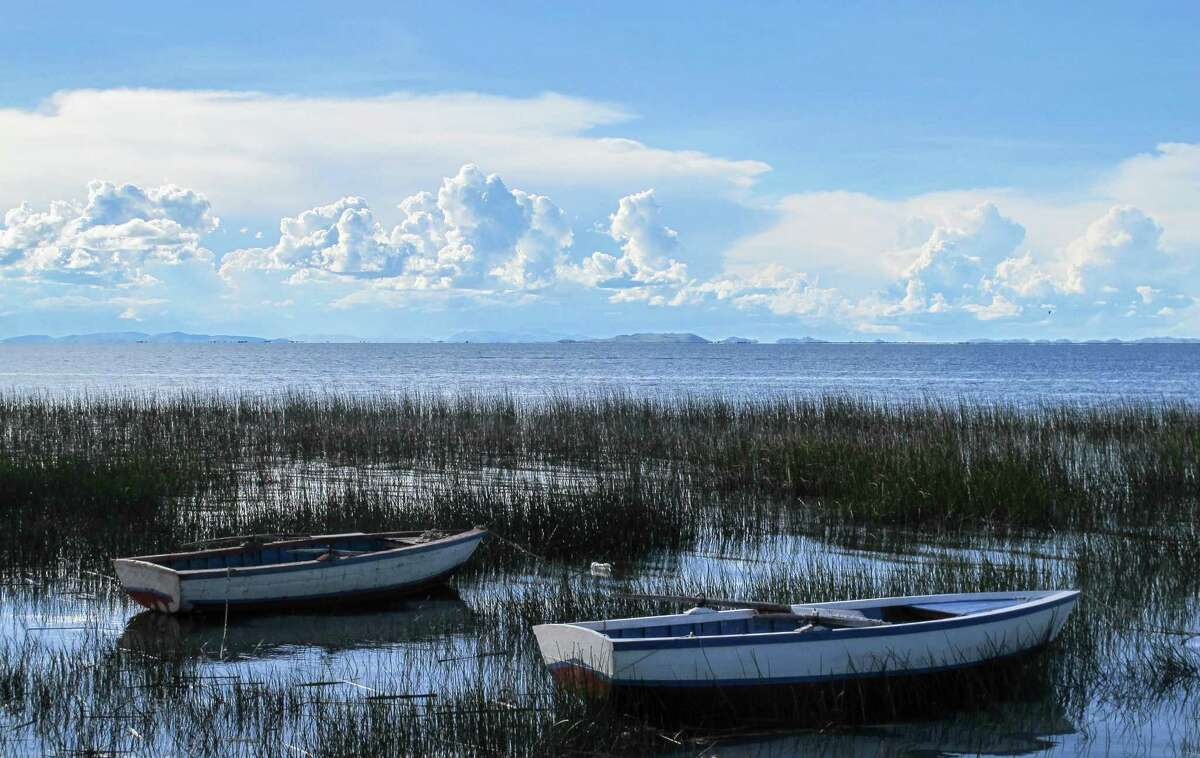 LAKE TITICACA, PERU - The residents of Luquina Chico anchor their row boats near the shore of their village which looks out upon the vast expanse of Lake Titicaca. By mid-afternoon, distance thunderheads create fantastic cloudscapes in the sky. (Thomas Curwen/TNS)