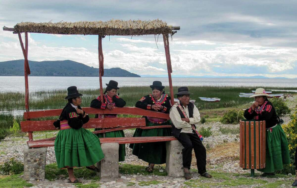 LAKE TITICACA, PERU - Traditionally dressed, the men and women of Luquina Chico, who invited visitors in their homes, gather on the shore of Lake Titicaca to say goodbye to their guests. (Thomas Curwen/TNS)
