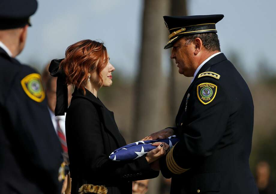Houston Police Chief Art Acevedo presents a flag to Houston Police Sgt. Christopher Brewster's widow, Bethany Elise Brewster, during a funeral service Thursday, Dec. 12, 2019, at Grace Church Houston in Houston. Brewster, 32, was gunned down Saturday evening, Dec. 7, while responding to a domestic violence call in Magnolia Park. Police arrested 25-year-old Arturo Solis that night in the shooting death. Solis faces capital murder charges. (Godofredo A. Vasquez/Houston Chronicle via AP) Photo: Godofredo A. Vasquez/Associated Press
