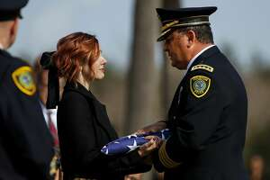 Houston Police Chief Art Acevedo presents a flag to Houston Police Sgt. Christopher Brewster's widow, Bethany Elise Brewster, during a funeral service Thursday, Dec. 12, 2019, at Grace Church Houston in Houston. Brewster, 32, was gunned down Saturday evening, Dec. 7, while responding to a domestic violence call in Magnolia Park. Police arrested 25-year-old Arturo Solis that night in the shooting death. Solis faces capital murder charges. (Godofredo A. Vásquez/Houston Chronicle via AP)
