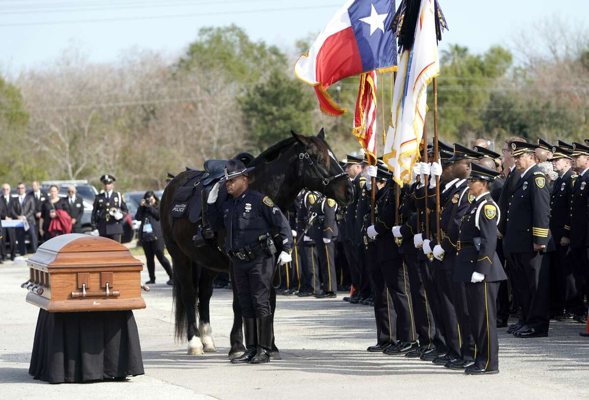 A member of the Houston Police Mounted Patrol pauses to salute as he leads a riderless horse past the casket of Houston Police Sgt. Christopher Brewster during a funeral service Thursday, Dec. 12, 2019, at Grace Church Houston in Houston. Brewster, 32, was gunned down Saturday evening, Dec. 7, while responding to a domestic violence call in Magnolia Park. Police arrested 25-year-old Arturo Solis that night in the shooting death. Solis faces capital murder charges. (AP Photo/David J. Phillip)