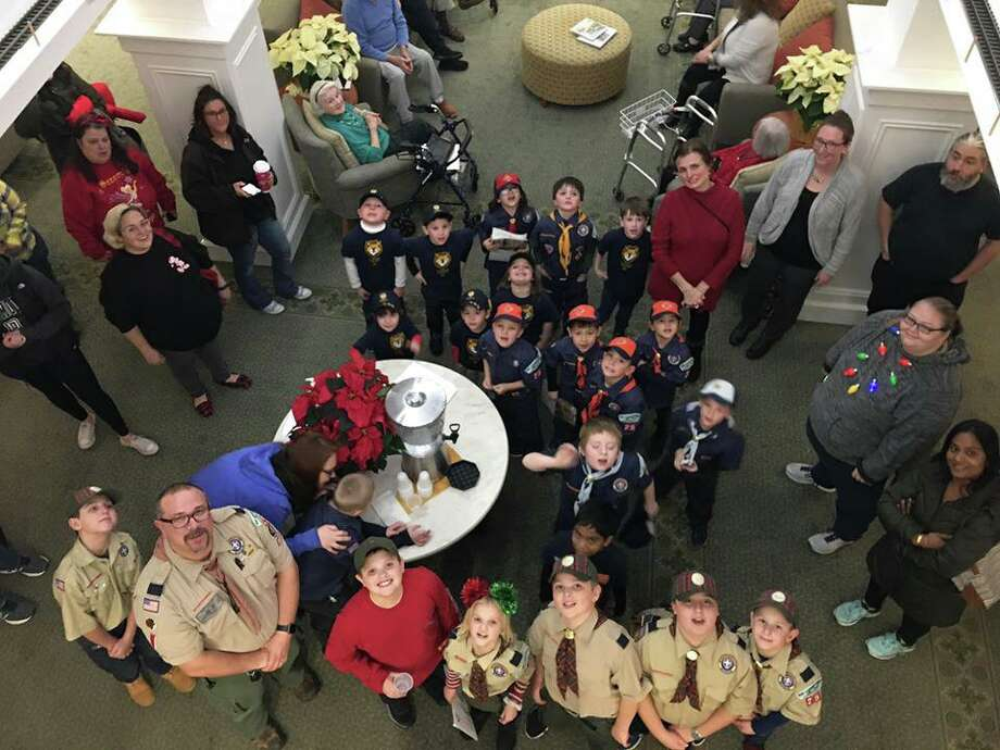 Scouts from local Pack 25 helped residents at Crosby Commons kick off the holiday season with an evening of decorating, songs and Christmas cookies. Photo: Contributed Photo / Connecticut Post