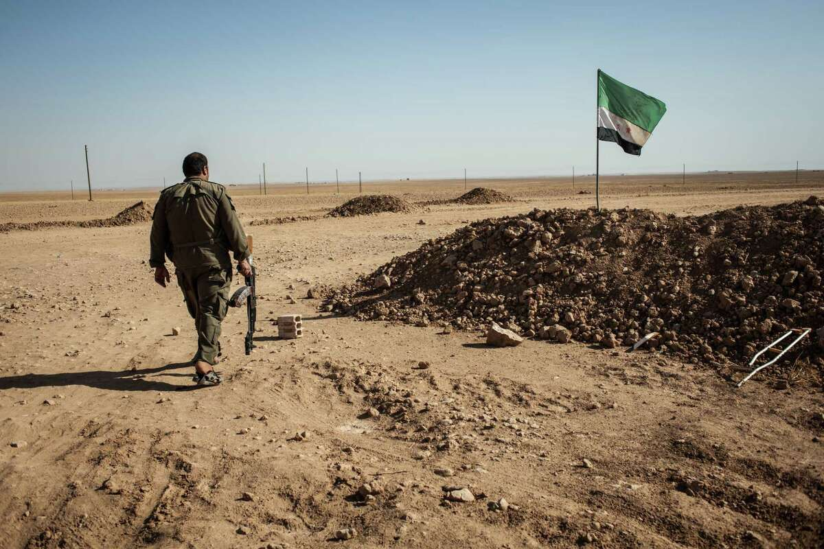 A Syrian fighter takes up his position in the countryside of Raqqa province as his group battles the Islamic State in 2015. Various armed groups, including Kurds and Arabs, joined in the efforts to defeat the extremist militants in Iraq and Syria. (Alice Martins/The Washington Post)