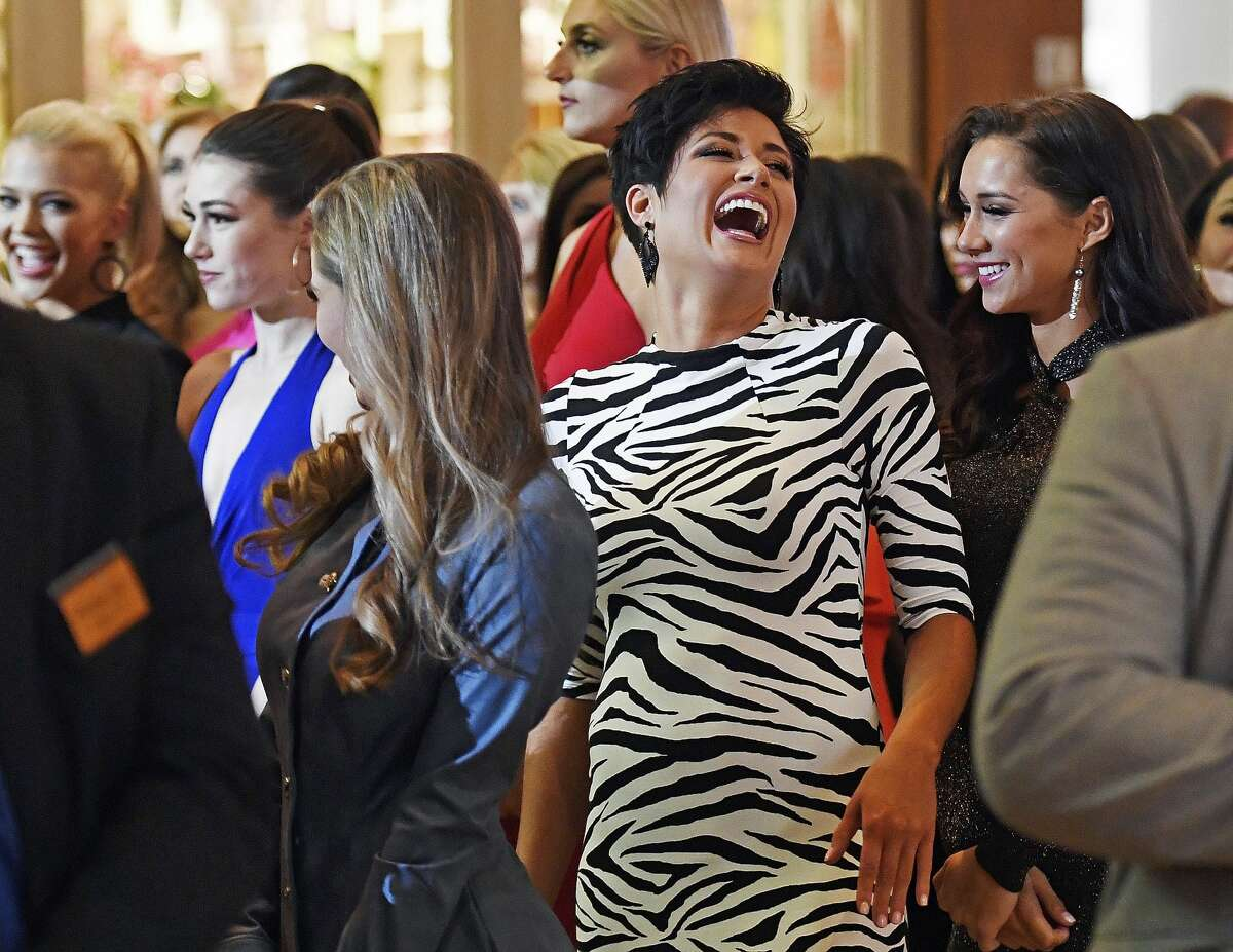 Miss Georgia, Victoria Hill, center, shares a laugh with Miss Hawaii, Nicole Holbrook, right, as the 51 candidates for Miss America 2020 wait to take the stage during the official Arrival Ceremony for the Miss America 2.0 competition Thursday, Dec. 12, 2019 at Mohegan Sun. The annual competition, in its 99th year, moved from Atlantic to Mohegan Sun this year. The candidates will face a series of preliminary competitions over the coming week culminating in the final competition on live TV next Thursday. (Sean D. Elliot/The Day via AP)