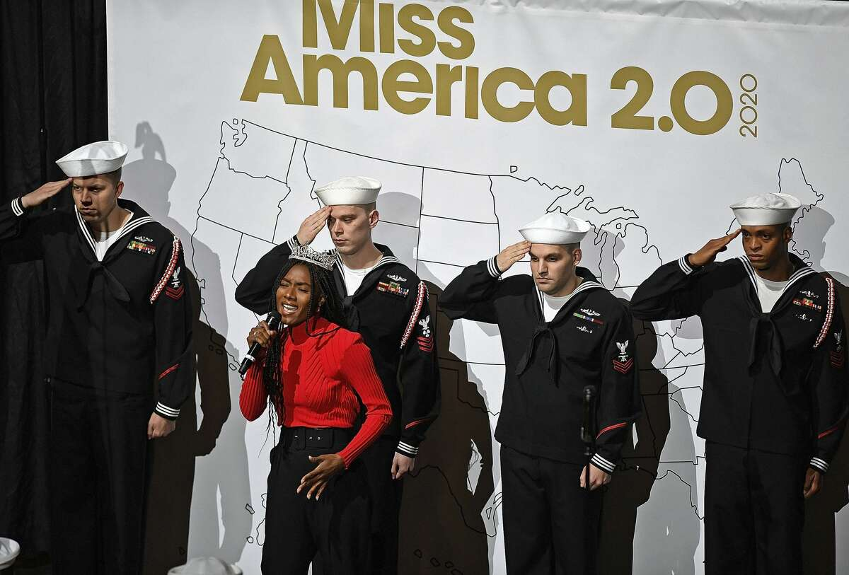 Sailors from the U.S. Navy salute as Miss America 2019 Nia Franklin sings the national anthem to pen the official Arrival Ceremony for the 51 candidates for Miss America 2020 Thursday, Dec. 12, 2019 at Mohegan Sun. The annual competition, in its 99th year, moved from Atlantic to Mohegan Sun this year. The candidates will face a series of preliminary competitions over the coming week culminating in the final competition on live TV next Thursday. (Sean D. Elliot/The Day via AP)