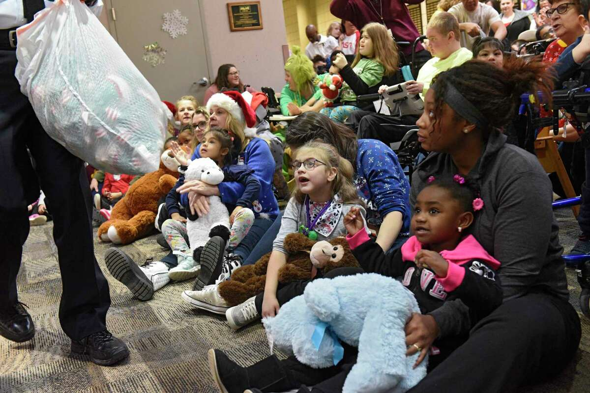Members of Police Athletic League (PAL) distributed presents to children at Center for Disability Services on Friday, Dec. 13, 2019 in Albany, N.Y. (Lori Van Buren/Times Union)