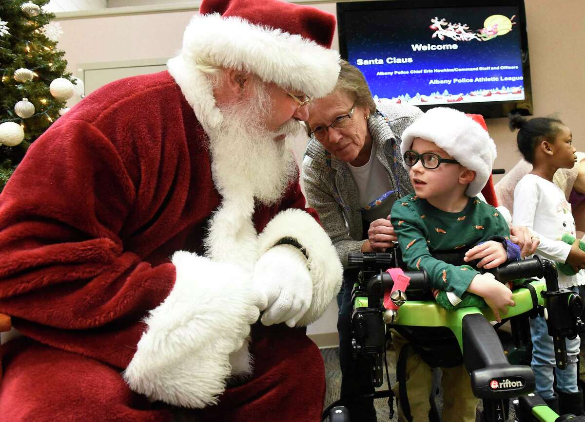 With his teacher Kathleen Kennedy behind him, Killian Polario, 4, visits with Santa Claus at Center for Disability Services on Friday, Dec. 13, 2019 in Albany, N.Y. Police Athletic League (PAL) members distributed presents to children at the center. (Lori Van Buren/Times Union)