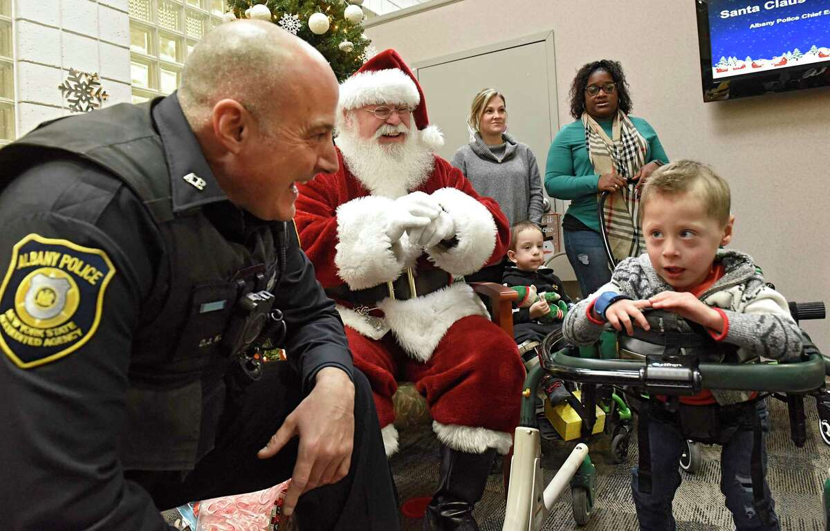 Police officer Daniel Kuhn, left, says hello to his nephew Jack Spring, 3, while Jack was visiting with Santa Claus at Center for Disability Services on Friday, Dec. 13, 2019 in Albany, N.Y. Police Athletic League (PAL) members distributed presents to children at the center. (Lori Van Buren/Times Union)