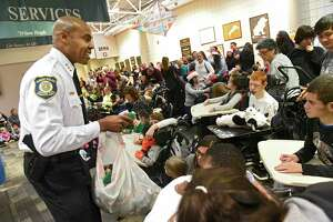 Albany Police Chief Eric Hawkins delivers presents to children during a visit at Center for Disability Services on Friday, Dec. 13, 2019 in Albany, N.Y.  Police Athletic League (PAL) members distributed presents to children at the center. (Lori Van Buren/Times Union)