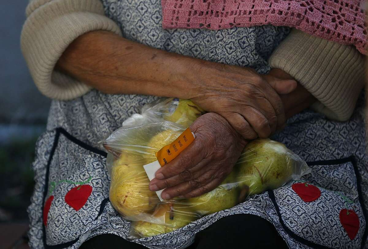 A woman holds a bag of pears as she waits in line at a food bank. Research shows that the financial scarcity focuses the mind. But that increased focus comes at a cost. By tunneling our vision on some things, we lose the ability to deal rationally with others.